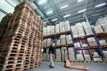 worker,hand pallet truck, stack of wooden pallets in storehouse
